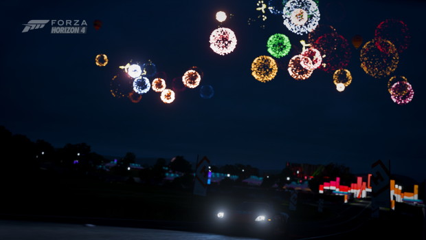 Image description: A car is driving at night with only it's headlights to show the road ahead, a festival area that has many vivid lights and fireworks in the sky is behind the car.