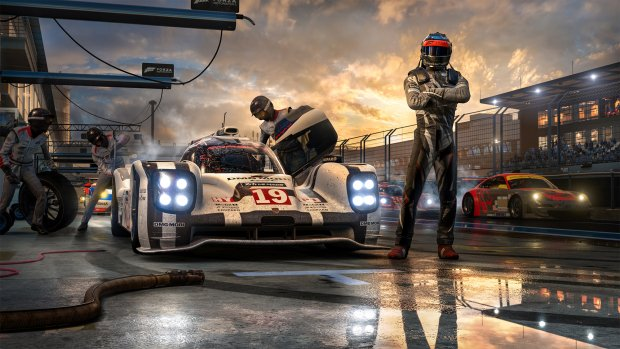 Image description: Promotional artwork for Forza Motorsport 7. A person in a track racing outfit stands in front of the camera with crossed arms, while the pit crew works on their car behind them.